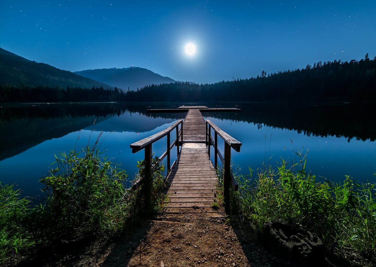 A scene at dusk as the moon rises above a lake. This image illustrates the importance of wills and probate legal advice after major trauma injuries