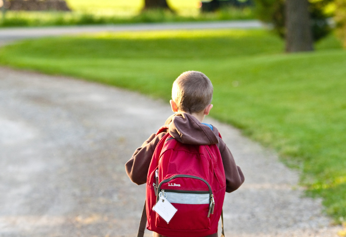 A boy walks alone as he carries his backpack to school illustrating the importance of focusing on special educational needs after major trauma injuries