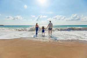 A family hold hands at the beach as the sun shines above, this image illustrates the importance of welfare benefits for family life
