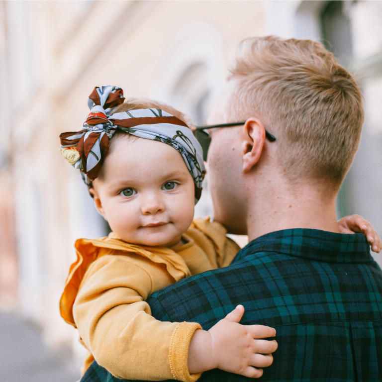 A baby held by her Father illustrating the importance of family and the impact major trauma injuries can have on the family unit
