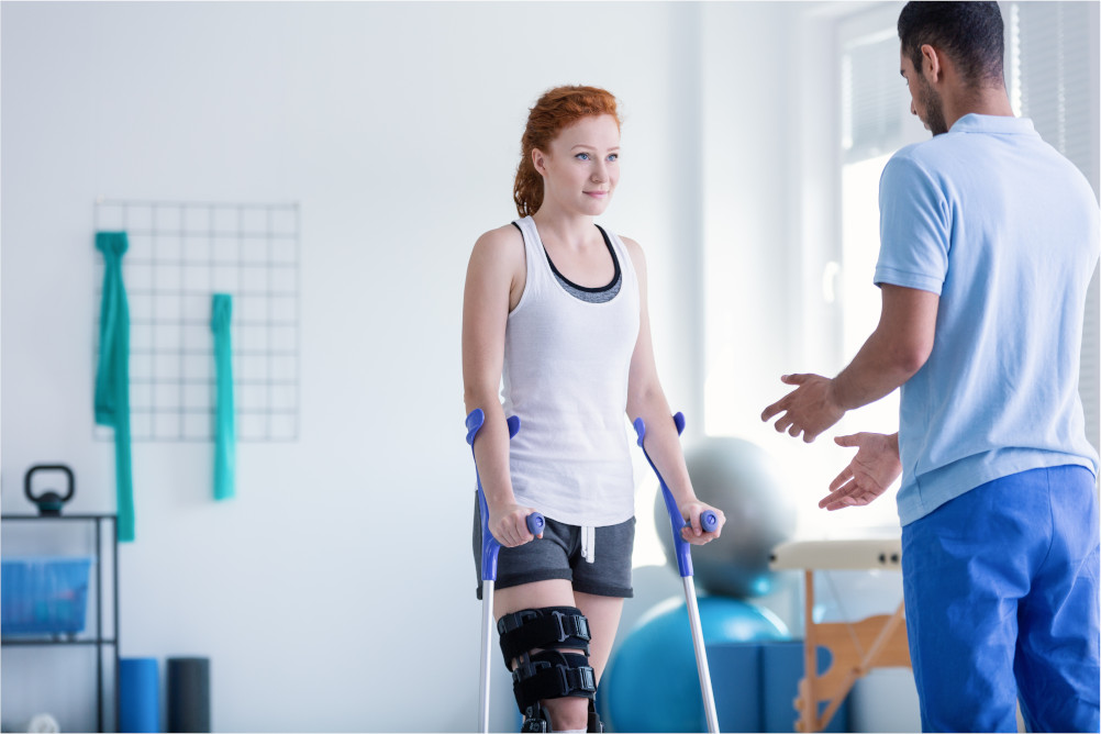 A patient on crutches with a knee brace undergoing rehabilitation from major trauma injuries with the help of a rehabilitation specialist