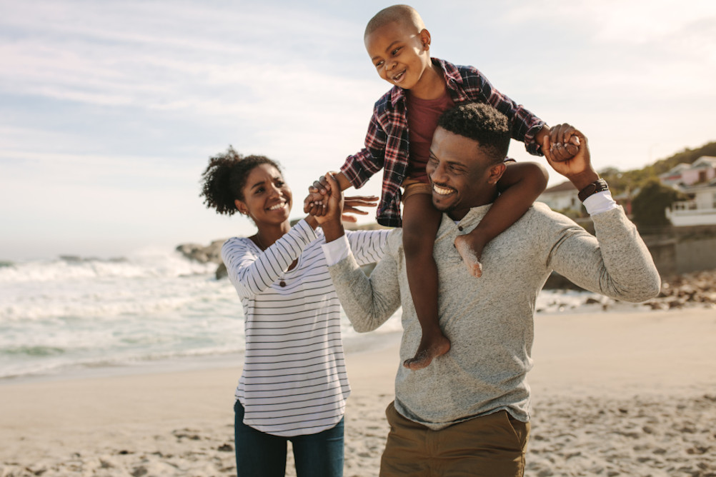 A family enjoy time together at the beach illustrating the importance of accurate financial planning advice after suffering major trauma injuries
