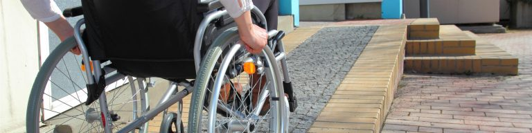 A person who has major trauma injuries in a wheelchair heading up a ramp into their newly adapted home