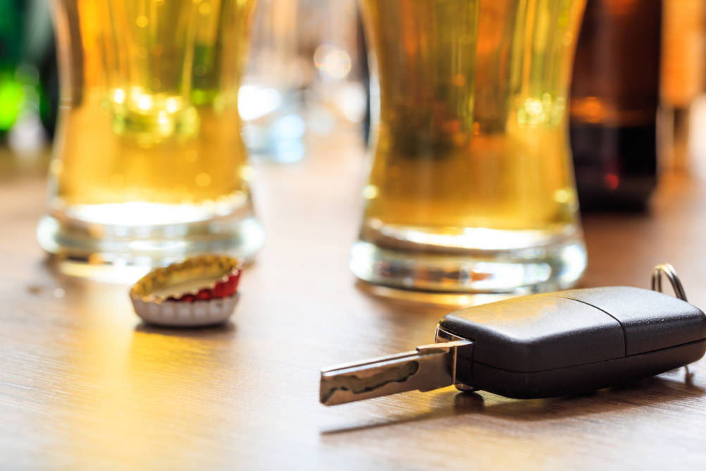 Pints of beer with car keys in the foreground signifying the dangers of drink driving