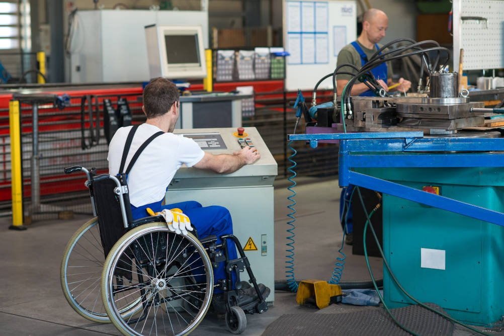 An employee working from a wheelchair at a height adjusted control platform illustrating the reasonable adjustments required when returning to work from major trauma injuries