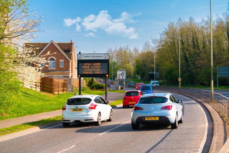 Vehicles pass an electric sign urging people to only make essential journeys thus illustrating the risks of overwhelming the NHS due to an increase in road accidents resulting in major trauma injuries