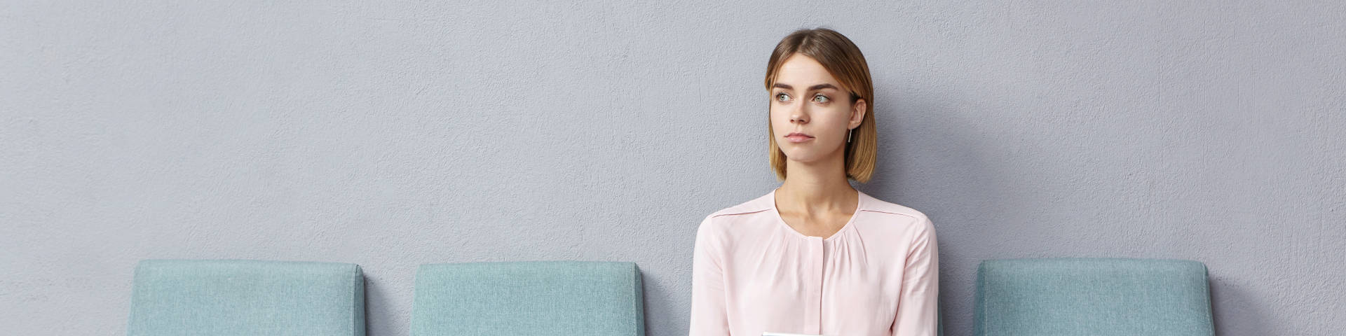 A lady sits on a chair in a waiting room looking pensive illustrating the importance of the limitation period in time limits for compensation claims
