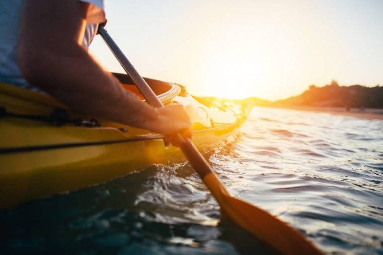 A kayaker paddles into the sunset illustrating our below the knee case study where the person who suffered the major trauma injury was a keen kayaker