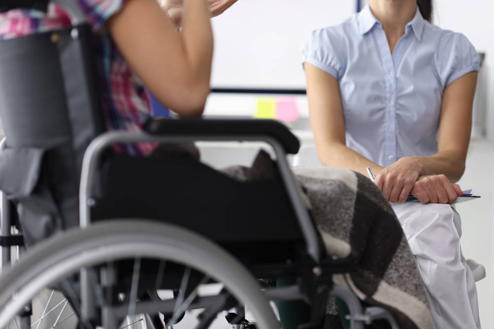 A lady in a wheelchair with major trauma injuries talks with a psychotherapist illustrating the psychological impact of major trauma