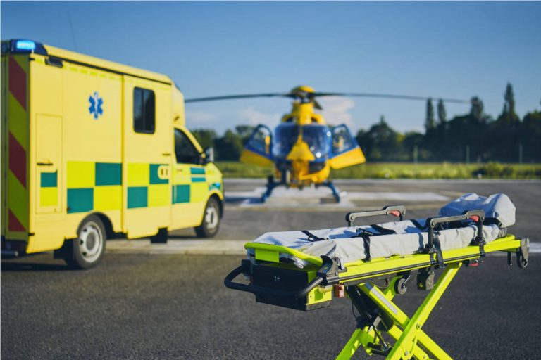 A road ambulance and an air ambulance alongside a hospital trolley illustrating our look at what major trauma actually means