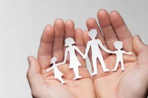 A paper cutout family in the palm of someone's hands illustrating the importance of choosing the right solicitor after major trauma