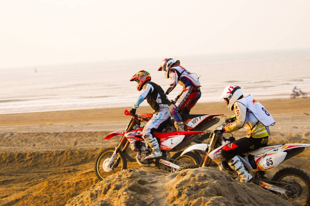 People on motorbikes take part in a motocross beach event illustrating our story about John and how he received early rehabilitation after sustaining multiple serious injuries in a motocross accident