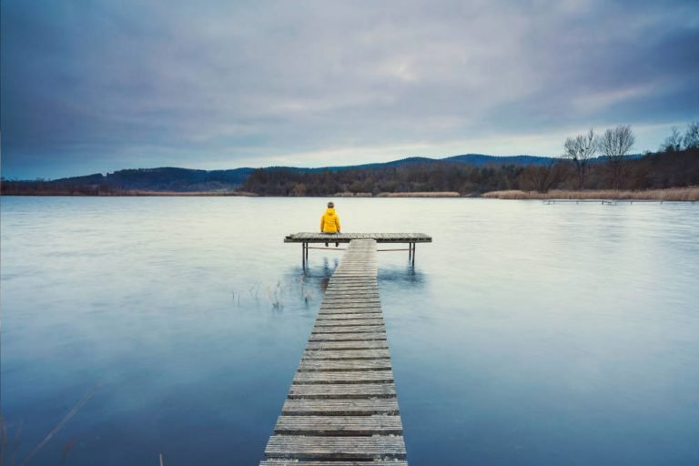 A lady sits alone by a lake illustrating the feelings of loneliness and fear around supporting a loved one in 24 hour care