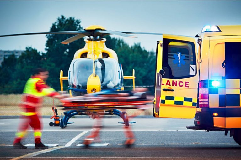 A paramedic delivers a patient from an ambulance to a waiting air ambulance illustrating the importance of the Air Ambulance service and the ambulances of the NHS and how the NHS Costs Recovery Scheme can help the NHS