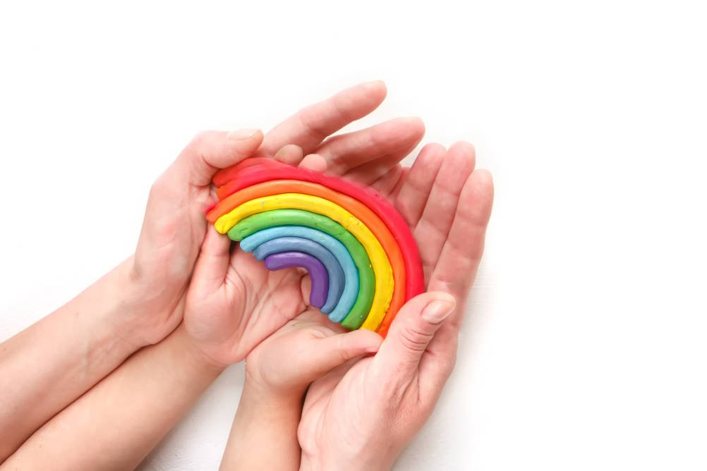 An adult's hands cup a younger person's hands whilst they are holding a rainbow made of plasticine illustrating the need for continued care and support to protect the NHS at a time when it is under pressure