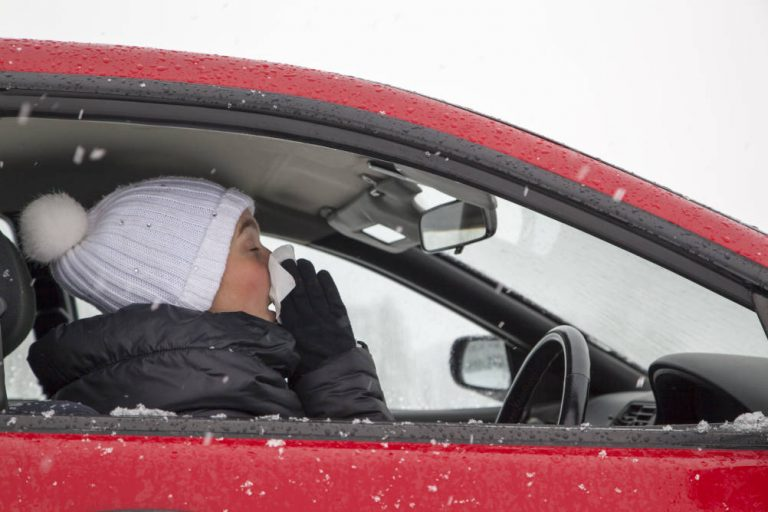 A lady sneezing whilst at the wheel of her car illustrating the issue of sneezing whilst driving and causing an accident
