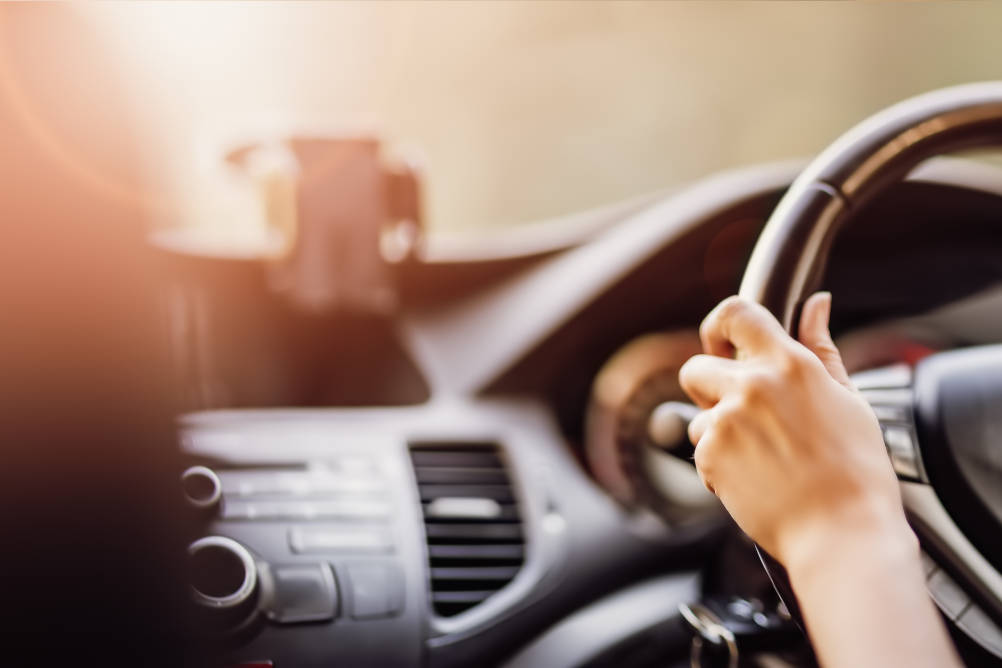 A driver with their hands on the steering wheel whilst their phone is cradled on the dashboard illustrating the dangers of driving whilst distracted